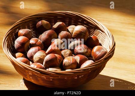 Haselnüsse in einem Korb auf einem Holztisch - Stockfoto
