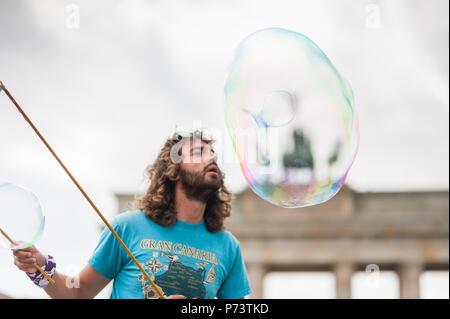 Bunte Seifenblasen schweben in den Vordergrund. Street Performer, Gaukler, unterhaltsam ist der Gast vor dem Brandenburger Tor in Berlin. - Stockfoto