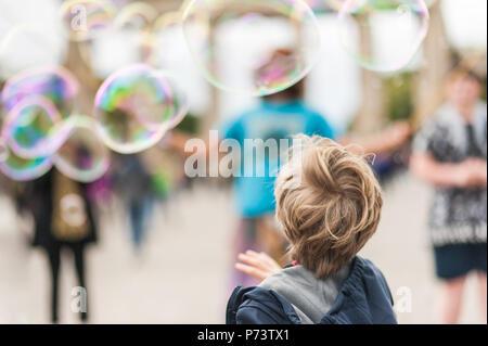 Kinder spielen mit bunten Seifenblasen. Street Performer unterhaltsam die Menschenmenge vor dem Brandenburger Tor in Berlin, bewölkten Sommertag. - Stockfoto