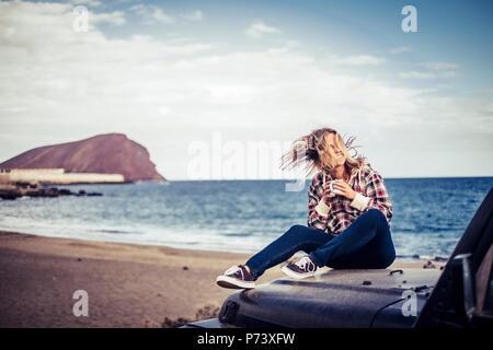 Gerne schöne blonde Mädchen Aufenthalt im Freien genießen das Wetter und die Reisen mit off road Black Car. wanderlust Konzept auf dem Sand bei t geparkt