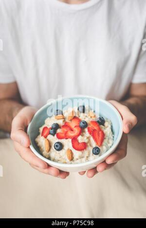 Männliche Hände, die haferflocken Schüssel Haferbrei mit frischen Beeren und Nüssen. Veganes Frühstück, gesunde Lebensweise und eine gesunde Ernährung Konzept - Stockfoto