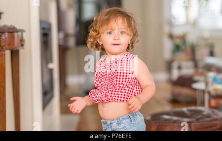 Schöne blonde Kind mit blauen Augen stehend angezeigt Bauchnabel zu Hause. - Stockfoto