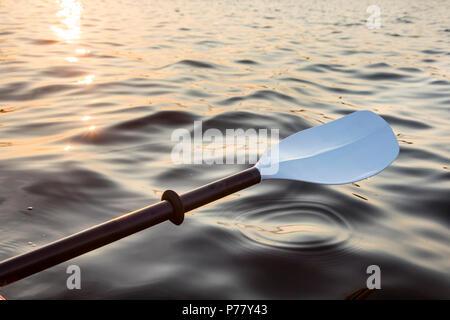 Kajak Paddel, mit bunten Sonnenuntergang Spiegelung auf dem Wasser. - Stockfoto