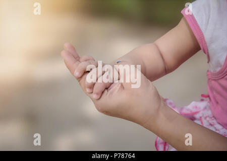Die Mutter, die ihr Baby hand Close-up. - Stockfoto