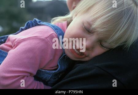 Kleines Mädchen weinend auf Mutters Schulter - Stockfoto