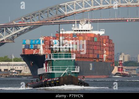 Tug James E. Brown; Container schiff ZIM Shanghai der ausgehende Port Elizabeth für den New Yorker Hafen, Bayonne Bridge und Newark Bay in der Ferne. - Stockfoto