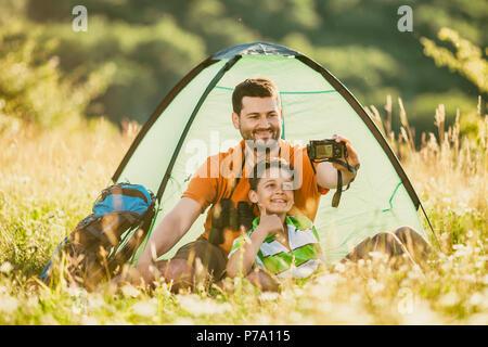 Vater und Sohn sind Camping in der Natur. Sie nehmen selfie. - Stockfoto