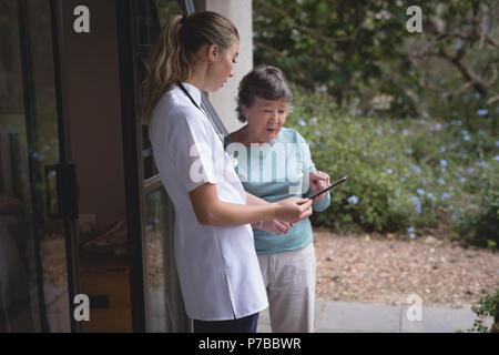Physiotherapeut und ältere Frau mit einem Tablet - Stockfoto