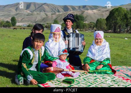 Kasachische Familie in traditioneller Kleidung, Zuhören, Akkordeon spieler, für redaktionelle nur, Sati Dorf, Tien Shan Gebirge, Kasachstan verwenden - Stockfoto