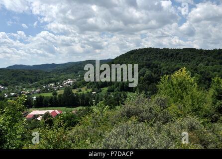 Die malerische Landschaft des ländlichen Raums in Rumänien, mit Hügeln und Häuser an einem bewölkten Himmel Hintergrund - Stockfoto