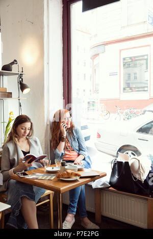 Frauen Lesen und Plaudern auf Handy im Cafe - Stockfoto