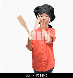 Dunkelhaarige kleine Kind tragen Küchenchef gleichmäßige Abdeckung Mund mit der Hand mit Schande für den Fehler, den Ausdruck von Angst erschüttert, die in der Stille Angst, geheime Conc - Stockfoto