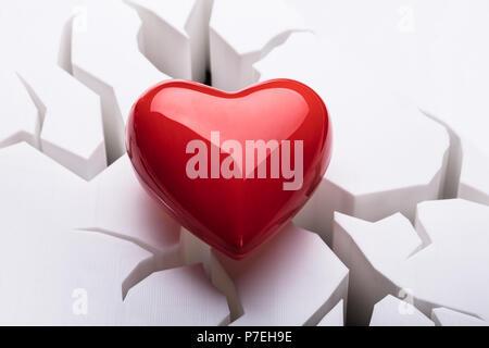 Hohe Betrachtungswinkel von roten Herzen auf Risse im weißen Hintergrund - Stockfoto