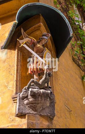 Fuggerei, Augsburg, Bayern, Deutschland - Darstellung des Erzengels Michael im Kampf gegen die Teufel an der Ecke eines Hauses. - Stockfoto