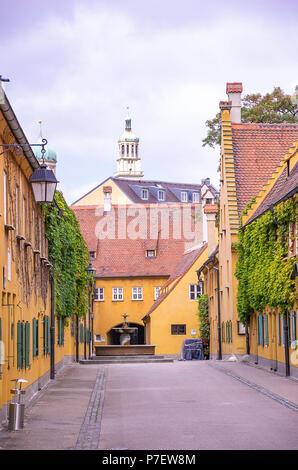 Fuggerei, Augsburg, Bayern, Deutschland - Blick durch die Mittlere Gasse Gasse zu den Brunnen und den Perlachturm Tower. - Stockfoto