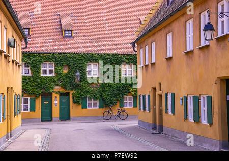 Fuggerei, Augsburg, Bayern, Deutschland - Blick durch eine der Gassen mit den armenhäusern. - Stockfoto