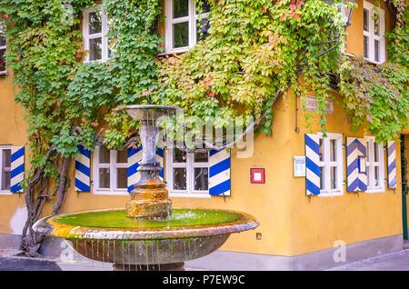 Fuggerei, Augsburg, Bayern, Deutschland - Zentrale Becken gut in der Herrengasse Gasse. - Stockfoto