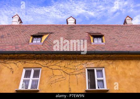 Augsburg, Bayern, Deutschland - 10. September 2015: Typische Obergeschoss Fassade und das Dach eines der armenhäusern in der Fuggerei sozialen Wohnungsbau. - Stockfoto