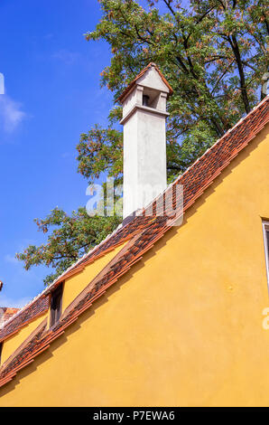 Augsburg, Bayern, Deutschland - 10. September 2015: Blick auf typische Dach Architektur mit Kamin in der Fuggerei sozialen Wohnungsbau. - Stockfoto
