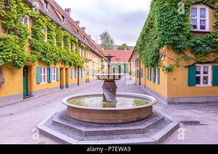 Augsburg, Bayern, Deutschland - 10. September 2015: Brunnen in der Herrengasse Gasse in die Fuggerei sozialen Wohnungsbau. - Stockfoto
