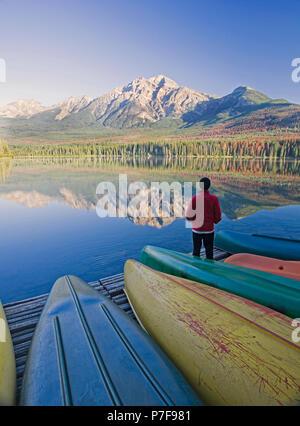 Einsame mittleren Alter Mann stehend auf Dock mit Kanus bei Pyramid Mountain im Pyramid Lake, Jasper National Park, Alberta, Kanada. - Stockfoto
