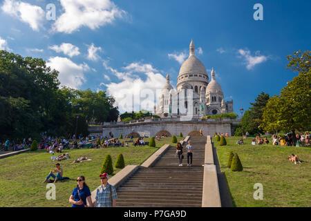 Paris, Frankreich, 25. Juni 2018: Menschen entspannend auf dem Gras vor der Basilika Sacré-Coeur in Montmartre - Stockfoto