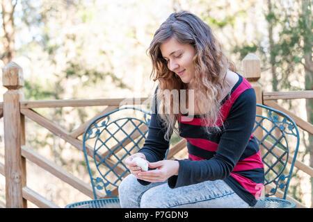 Eine junge Frau sitzt auf einem Stuhl, Holding, essen Stück hausgemachten Mochi klebrige glutenhaltigen Japanischen Reis Kuchen Dessert draussen, draußen auf Deck - Stockfoto