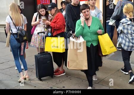 Käufer und Touristen die Einkaufstaschen zu Fuß vorbei am Kaufhaus Selfridges in der Oxford Street in Central London. - Stockfoto