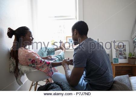 Liebevolle junge Paar Hände halten im Schlafzimmer - Stockfoto