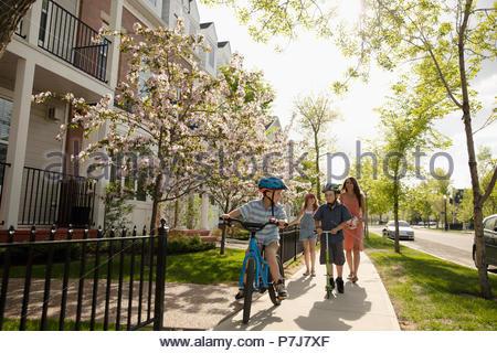 Mutter und Kinder reiten Fahrräder und Motorroller an sonnigen Nachbarschaft Bürgersteig - Stockfoto