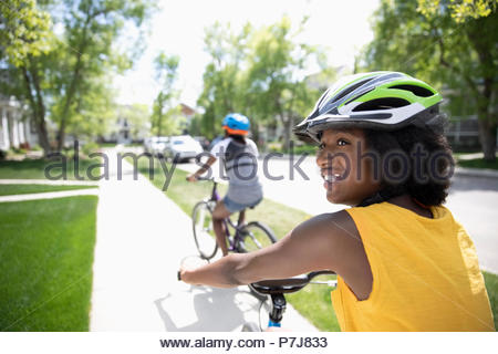 Lächelnd tween Girl in Helm Fahrrad fahren an sonnigen Nachbarschaft Bürgersteig - Stockfoto