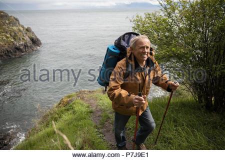 Active Senior Mann mit Rucksack auf einer Klippe mit herrlichem Blick auf den Ozean - Stockfoto
