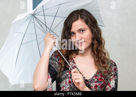 Porträt der jungen Frau im Studio Zimmer holding Blitz weißen Regenschirm Objekt für professionelle Fotografie lächelnd - Stockfoto