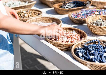 Nahaufnahme der jungen Frau Einkaufen für bunten Stein Strand Armbänder Hand berühren im freien Markt shop shop in Europäischen, Griechenland, Italien, Mediterranea - Stockfoto