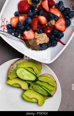 Vegetarisches Frühstück. Schüssel Hafer Müsli mit Milch, raw Himbeeren, Heidelbeeren, Erdbeeren, und Muttern mit Löffel für gesundes Frühstück und avokado - Stockfoto