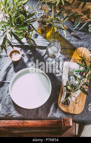 Tabelle einstellen. Aber abgesehen davon leeren Teller, Besteck und Olivenbaum Zweige Dekorationen auf grau Leinen Tischdecke. Kopieren Sie Platz. - Stockfoto