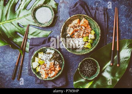 Hawaiian Lachs poke poce mit Avocado, Reis und sesamo in Schüsseln serviert auf tropische Blätter. Sushi Schüssel. Türkis schiefer Hintergrund. Ansicht von oben. - Stockfoto