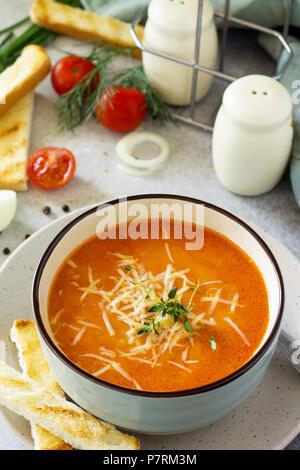 Püree mit Croutons Suppe Tomate und Käse in einer Schüssel auf einem hellen Schiefer Hintergrund. Das Konzept der gesunden Ernährung. Diätmenü. - Stockfoto