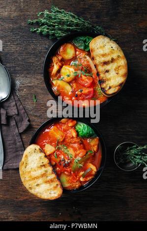 Italienische Suppe minestrone mit Gemüse der Saison auf einem dunklen Hintergrund, Ansicht von oben - Stockfoto