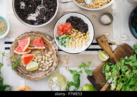 Zutaten zum kochen vegetarisch Salat mit schwarzen Quinoa, Kichererbse, Nüssen und Früchten auf Holztisch, Ansicht von oben. Superfood Konzept - Stockfoto