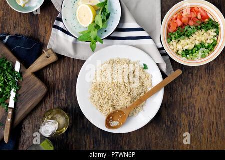 Gesunde Ernährung Konzept. Zutaten zum kochen vegetarisch Salat mit Porridge Bulgur und Gemüse auf Holztisch, Ansicht von oben - Stockfoto