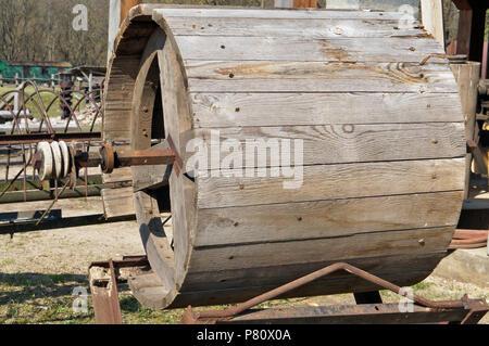 Eine große hölzerne Trommel für landwirtschaftliche Maschinen liegt in der Nähe des Dorfes Scheune installiert. Sonniger Frühlingstag Außenaufnahme - Stockfoto