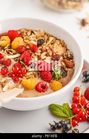 Smoothie Schüssel mit Bananen, Kakao, Beeren und hausgemachtem Müsli. Veganes Frühstück Banane Eiscreme. Gesunde vegane Ernährung Konzept. - Stockfoto