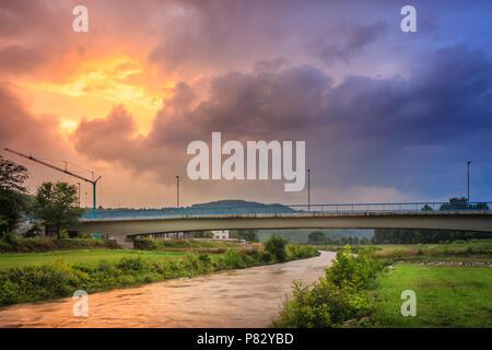 Dramatische, brennenden Sonnenuntergang Himmel über gazela Brücke und seidig, reflektierende Nisava Fluss in Pirot - Stockfoto