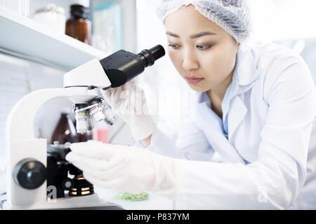 Wissenschaftlerin mit Mikroskop - Stockfoto