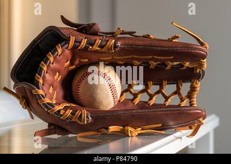Nahaufnahme einer verwendet baseball ball innerhalb Braun, Leder baseball Handschuh auf schlichten, grauen Hintergrund. - Stockfoto