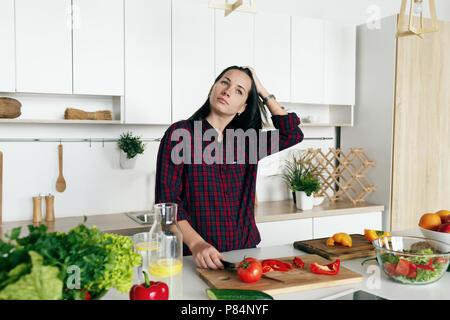 Frau bereitet Gemüse in der Küche zu Hause. Gesundes Essen zu Hause Konzept - Stockfoto