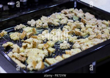 Cracker für Caesar Salat. Stück Brot auf Blech in Knoblauch Sauce - Stockfoto