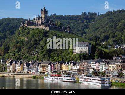 Das Schloss (Reichsburg), mit seinem Weinberg, ragt über bunten Fachwerkhäusern entlang der Ufer der Mosel in Cochem, Deutschland.