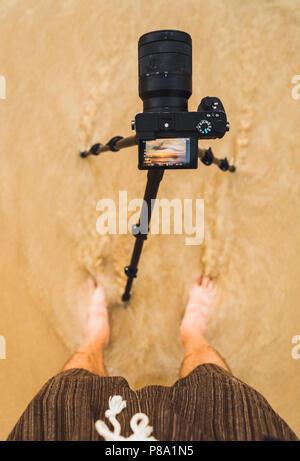 Von oben Mann mit Kamera in den nassen Sand an der Küste und schießen Sonnenuntergang in Bangkok, Thailand. - Stockfoto